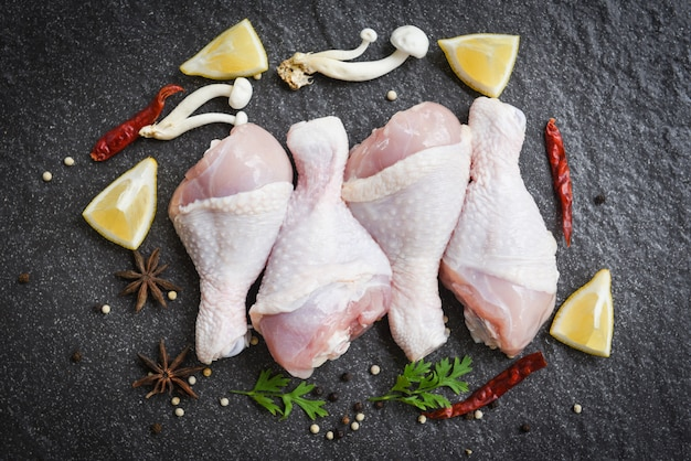 鶏肉の生脚、レモンチリハーブとスパイスとキノコの黒プレートトップビュー、生の鶏肉を調理用材料でマリネ
