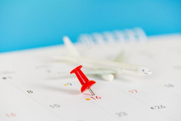 Планирование поездки с точками назначения самолета на булавке календаря, временем поездки или планом для концепции путешествия