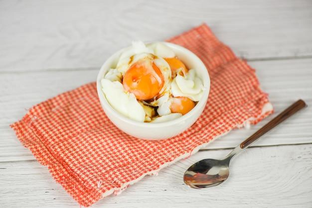 テーブルの背景、柔らかいゆで卵の朝食のボウルにゆで卵