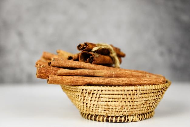Палочки корицы на корзине с травами и специями для приготовления