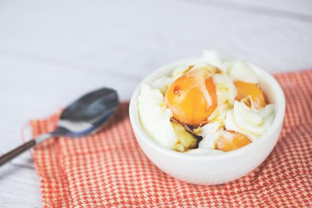 Вареное яйцо в миске с соусом для завтрака на столе