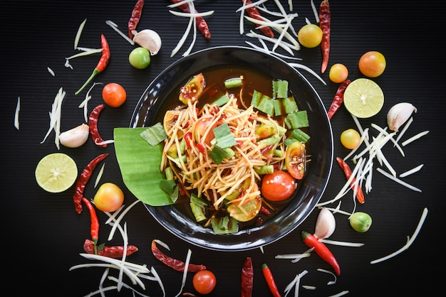 テーブルの上の緑のパパイヤサラダスパイシーなタイ料理