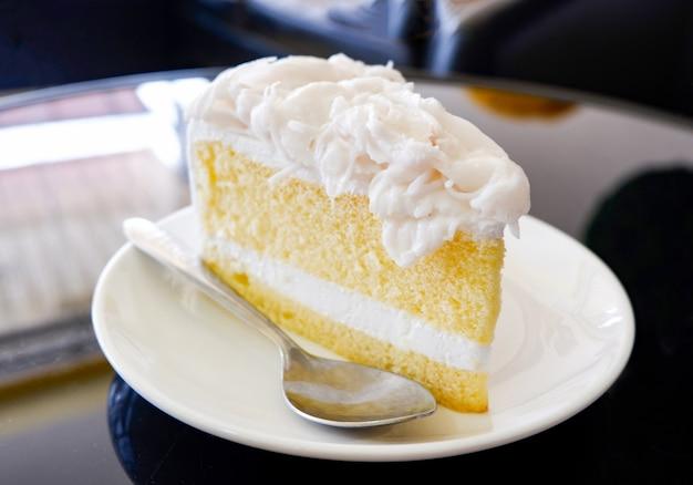白いプレートにケーキスライスクリームバニラケーキスライスコーヒーショップでココナッツケーキミルクデザート