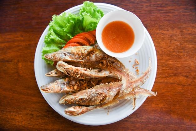 魚のフライ、野菜サラダトマトと白い皿木製テーブルのソース