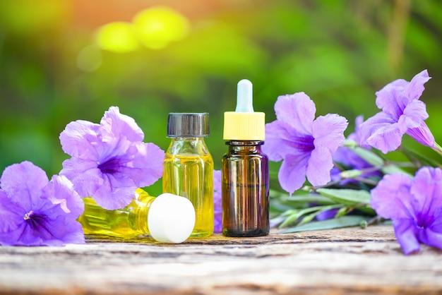 自然の緑に紫色の花とアロマセラピーハーブオイルボトルの香り