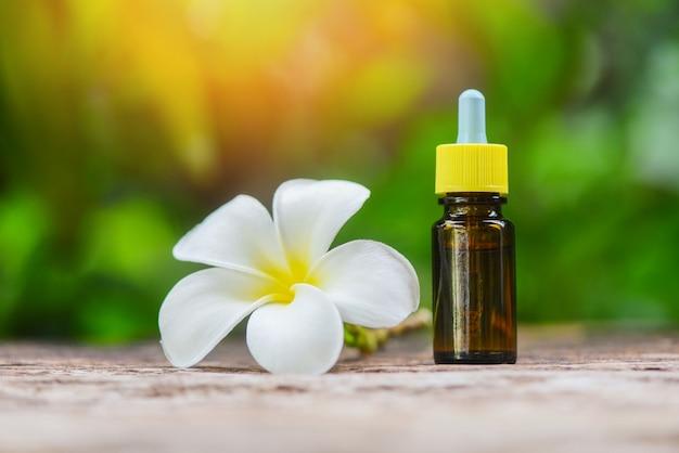自然緑の白い花フランジパニプルメリアオンとアロマセラピーハーブオイルボトルの香り