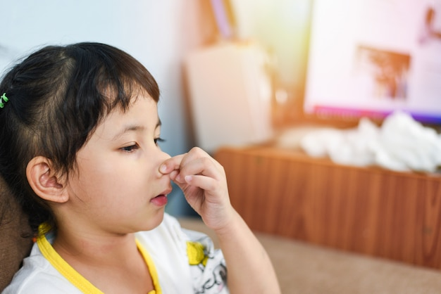 インフルエンザの季節に鼻を持っている手で病気のアジアの少女が風邪をひいて鼻をかむ、子供の鼻水とくしゃみが鼻と発熱を自宅で吹く
