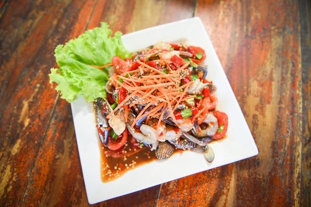 新鮮なエビカニ貝のスパイシーなシーフードサラダ、白い皿に添えて