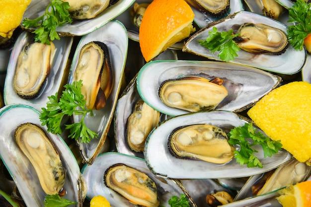 テーブルの設定でオレンジレモンパセリトマトと鍋にハーブとムール貝、蒸しムール貝の緑のシェルダイニングテーブルレストランでおいしいシーフードを提供