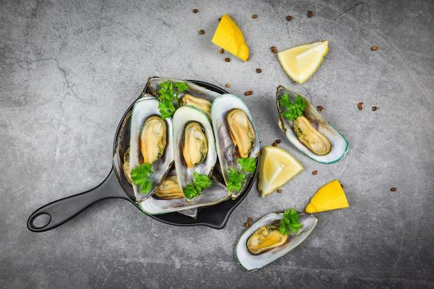 テーブルの設定でレモンパセリトマトと鍋にハーブとムール貝、蒸しムール貝のグリーンシェルダイニングテーブルレストランでおいしいシーフードを提供