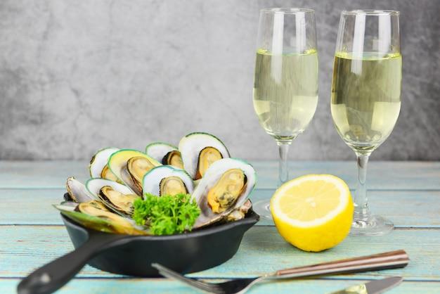 テーブルセッティングでのレモンパセリとムール貝、蒸しムール貝とワイングラスは、ダイニングテーブルレストランで美味しい白いプレートシーフードソースでお召し上がりいただけます
