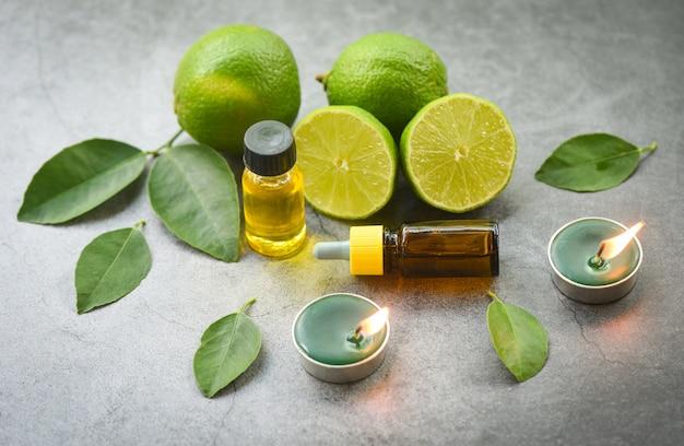 アロマセラピーハーブオイルボトルライムレモンとアロマキャンドルハーブトップビュー、黒と緑の葉の自然なエッセンシャルオイルとハーブの葉