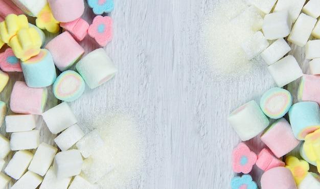 Белый сахар, кусочки сахара и красочные конфеты сладкие на фоне стола