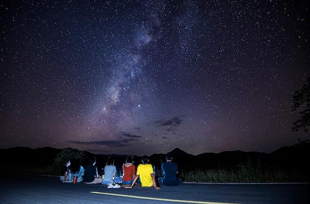 空の夜を見て道路に座っている観光客と天の川銀河