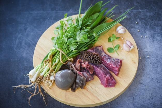 木製まな板の上のニンニクのスパイスと生肉牛肉