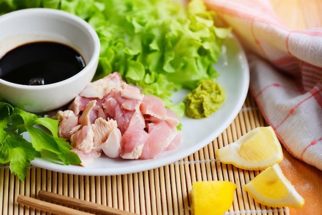 Сырая курица сашими на белой тарелке с соусом васаби и овощным салатом с чесноком, чили, травами и специями традиционная японская еда - кусочки куриного филе мяса