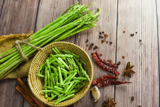 新鮮なアスパラガスの束とバスケットでのカット-アスパラガスのグリーンチリガーリックスパイスと料理用エシャロット