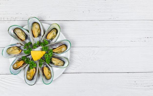 テーブルにレモンパセリとハーブとムール貝-レストランでの食事でおいしい白いプレートシーフードで蒸したムール貝
