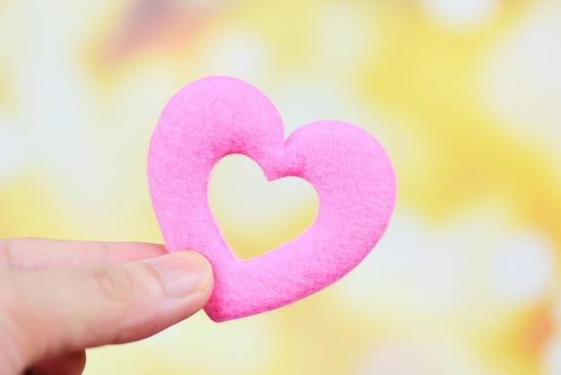 慈善の概念-バレンタインの日に手でピンクのハートを保持または寄付愛の暖かさを与える男の世話をする心