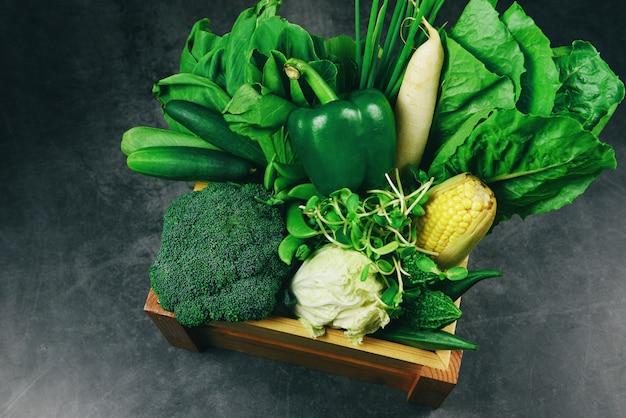新鮮な緑の果物と緑の野菜を市場で木箱に混ぜて、健康食品のさまざまなトップビュービーガンクック