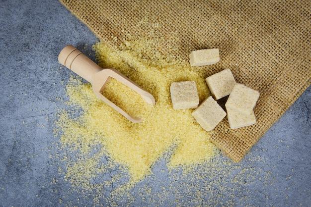 Коричневый сахар и кусочки сахара на мешке