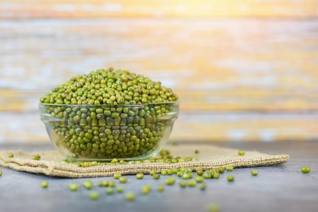 Зеленые бобы мунг в миске на мешке - зерновые бобы мунг цельные зерна