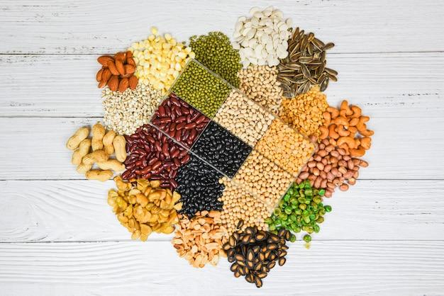 Набор различных цельных зерен бобов и семян бобовых семян чечевицы и орехов красочные закуски вид сверху - коллаж различные бобы смесь гороха сельского хозяйства натуральных здоровых продуктов для приготовления ингредиентов