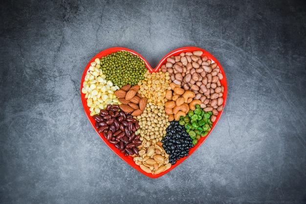 さまざまな豆のコラージュミックス食材の自然健康食品のエンドウ豆農業-異なる全粒豆とマメ科植物の種子レンズ豆と心の組成にカラフルなナッツのセット