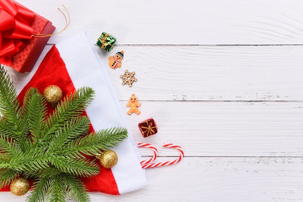 Новогодний праздник фон с колпак санта-клауса и еловые ветки украшения конфеты тростника сосны подарочной коробке и праздничный объект с новым годом