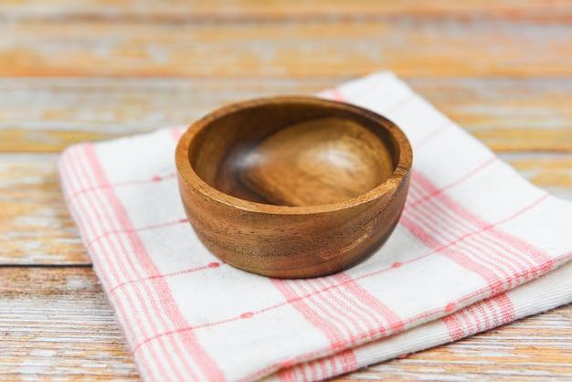 ダイニングテーブルの上のテーブルクロスのナペリーに空の木製ボウル