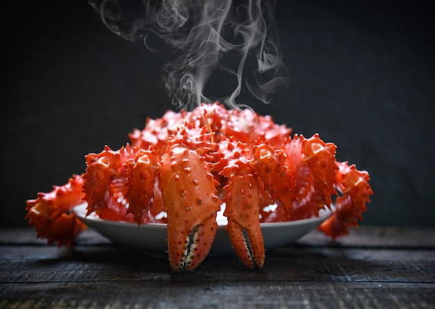 赤いカニ北海道-アラスカのタラバガニは、暗い背景に蒸気または煮魚介類を調理