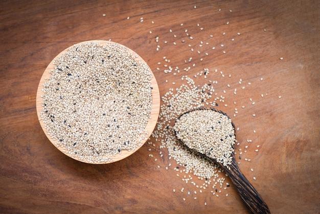 Семена кунжута в деревянной миске и ложке на фоне дерева стол