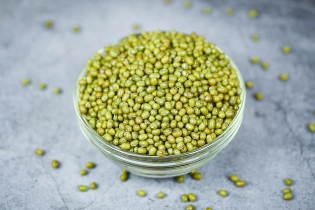 Зеленые бобы мунг в миске на серых зернах бобов мунг цельные зерна