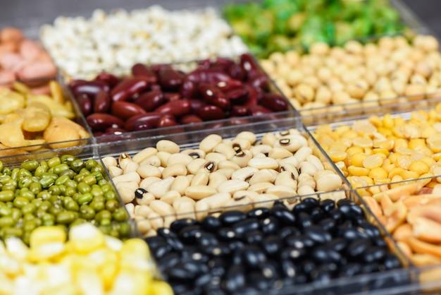異なる全粒豆とマメ科植物の種子レンズ豆とナッツのボックスカラフルなスナックトップビュー