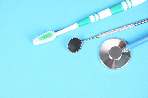 Инструменты стоматолога-стоматолога с зубными протезами и инструментами для гигиены полости рта и осмотра оборудования с помощью зеркала рта