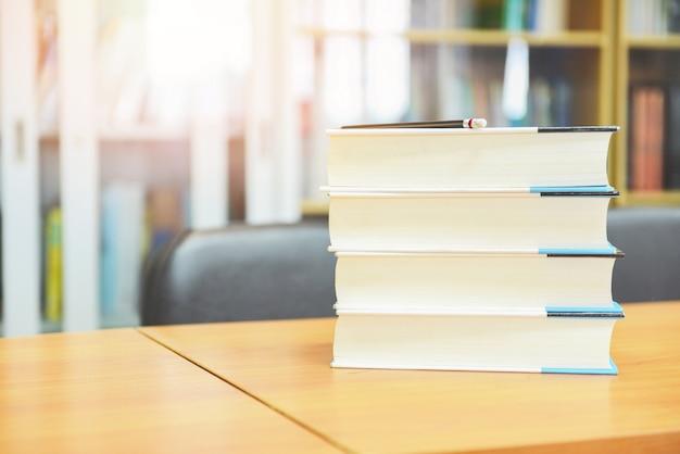 学校と研究に戻る教育コンセプト-鉛筆でテーブルに積み上げられた本と図書館の本