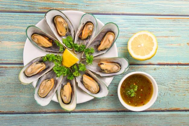 テーブルのレモンパセリとハーブとムール貝-ムール貝の蒸し蒸し
