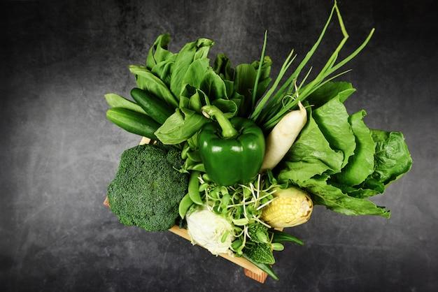 新鮮な緑の果物と緑の野菜を市場で販売するための木製の箱に混ぜて、健康食品ビーガンクックのさまざまなトップビュー/野菜の健康食品の選択をきれいに食べる健康