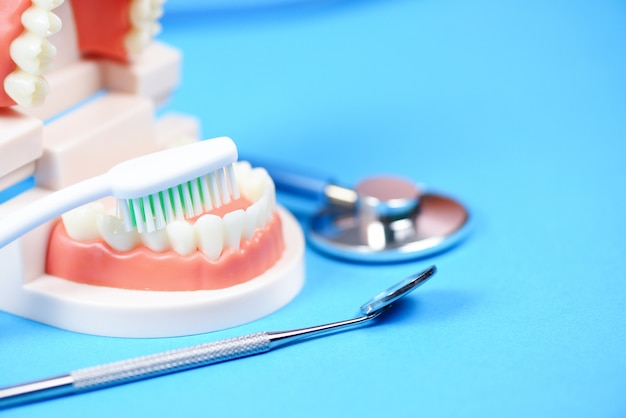 Концепция стоматологической помощи - инструменты стоматолога с зубными протезами, инструменты для стоматологии, а также проверка гигиены зубов и оборудования с моделью зубов и ротовой полостью рта