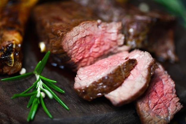 Жареное филе говяжьего стейка с зеленью и специями подается на деревянной доске - кусочек мяса говядины на гриле средне-редкий стейк рибай