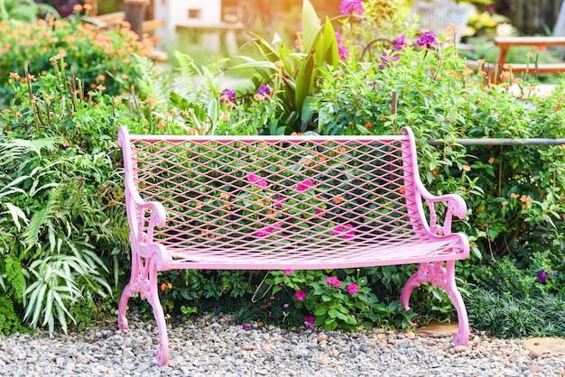 公園のベンチ-夏の緑の植物と花の背景と庭でピンクのヴィンテージベンチ椅子