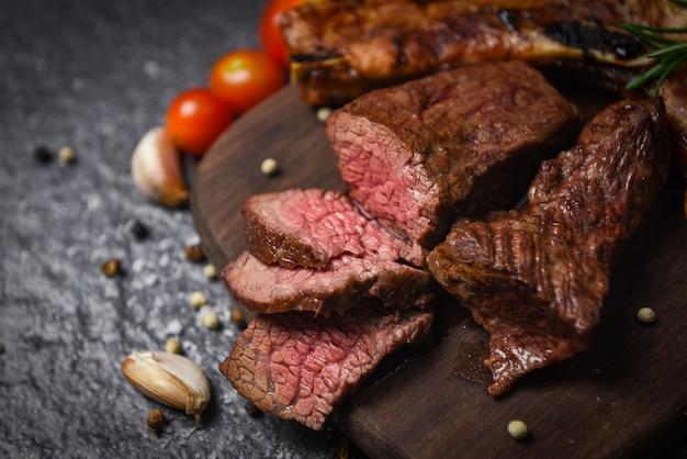 Жареное филе говяжьего стейка с зеленью и специями, подается с овощами на деревянной доске - кусочек мяса говядины на гриле на черной поверхности