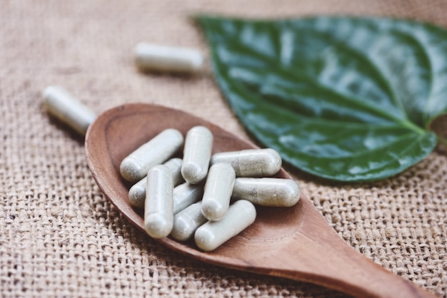Травяные лекарства / капсулы натуральной травы на деревянной ложке и зеленые листья на фоне мешка