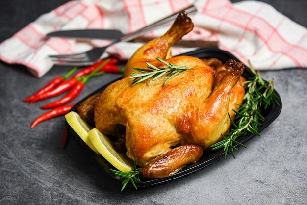 丸ごとローストチキンローズマリーとチリレモン-休日のダイニングテーブルで焼き鳥グリルバーベキューおいしい料理