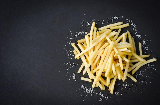 黒いプレートに塩と新鮮なフライドポテト、トップビューコピースペース-食べ物やスナックのおいしいポテトフライ