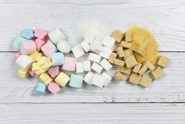 Белый сахар, кусочки сахара и красочные конфеты сладкие на фоне стола сверху