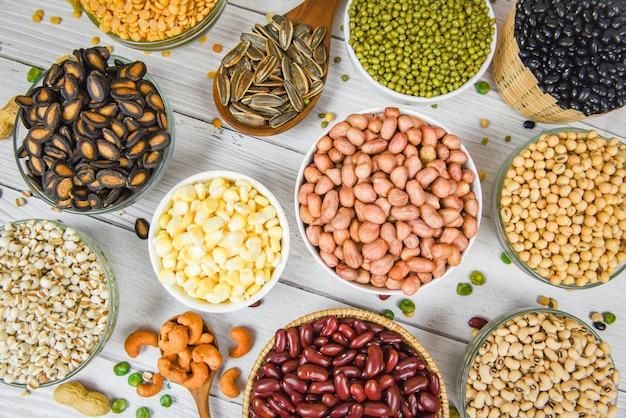 ボウルとマメ科植物の種子レンズ豆とナッツの異なる全粒豆のカラフルなスナック背景トップビュー-様々な豆ミックスエンドウ豆の農業成分の調理のための自然な健康食品の農業