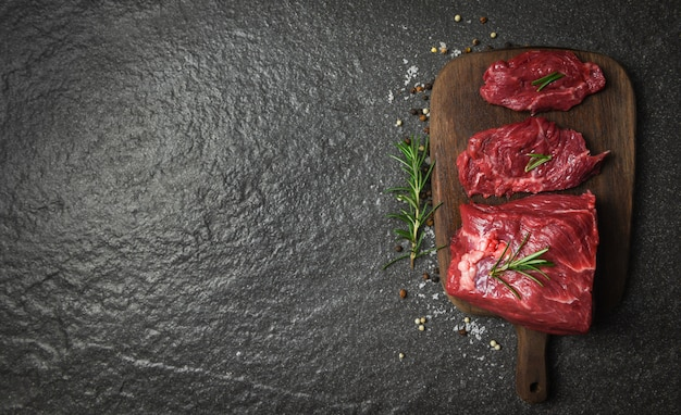 ハーブとスパイスのローズマリーと生の牛肉ステーキ/木製のまな板の背景にスライスした新鮮な肉牛肉