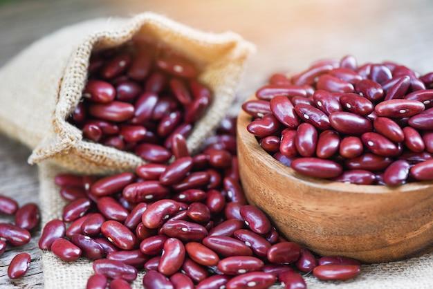 Красная фасоль в деревянной миске на фоне мешка / зерна красной фасоли /