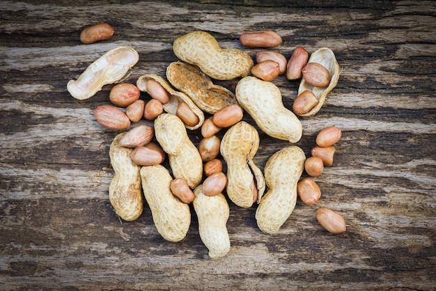食品やスナックの殻のピーナッツ/素朴な木製の背景にローストピーナッツ